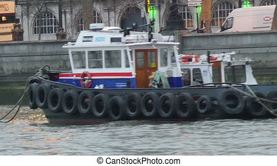A tug boat cruising on the Thames river