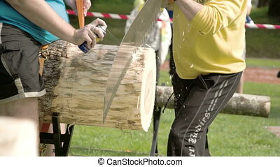 A man in yellow sweater is sawing the big log