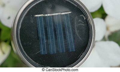 A black solar energy charger on a garden. The circle battery...