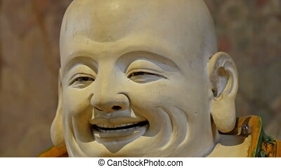 Statue of a bald man with fat face. Showing the smiling fat...