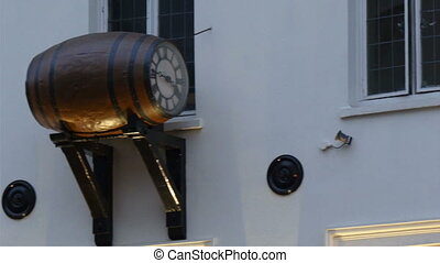 A clock on a barrel on a wall of the building This is one of...
