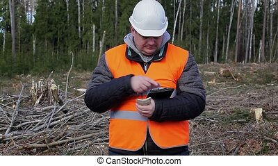 Lumberjack counting money in forest