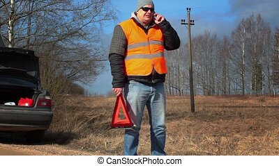 Man with warning triangle talking on the cell phone near car...