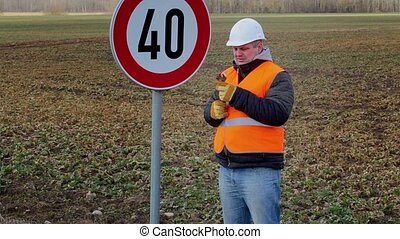Worker with adjustable wrench near road sign