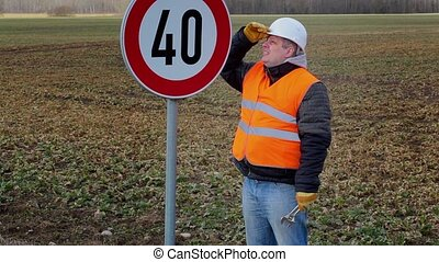 Worker working with adjustable wrench near road sign