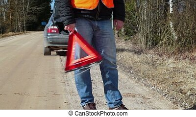 Nervous man with warning triangle on the road near car