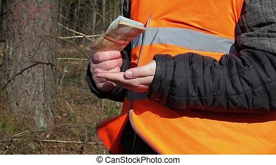 Worker with euro banknotes in forest