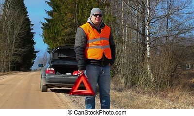 Man with warning triangle on the road near car