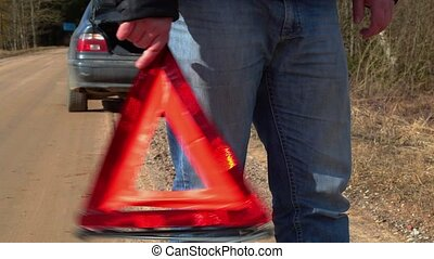 Man with warning triangle on the road