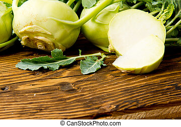 Kohlrabi - Photo of kohlrabi heads with slice on wooden...