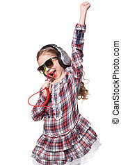 Pretty little girl singing in imaginary microphone with headphones on his head isolated over white background
