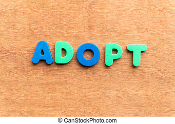 adopt colorful word on the wooden background