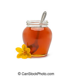 Pot of honey with spoon - A glass of golden honey with...