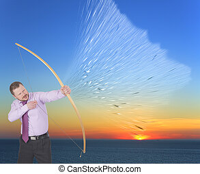 Businessman practicing archery on sunset background -...