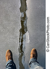 Cracked ice and man leg Danger background