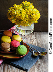 Spring time - Colorful macaroons and first spring flowers on...