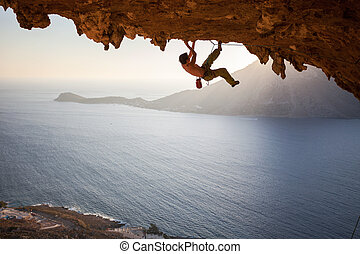 Rock climber climbing along roof in cave at sunset - Rock...