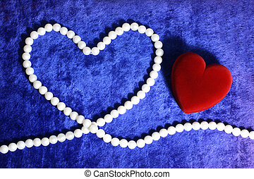 red heart and pearly neacklace on blue velvet