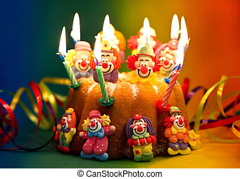 birthday cake with sugar clowns decoration and candles