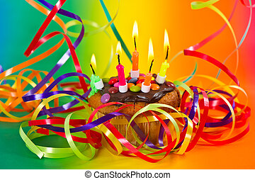 birthday cake with colorful streamer decoration and burning cand