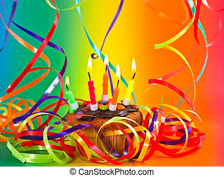 birthday cupcake with candles and colorful streamer decoration