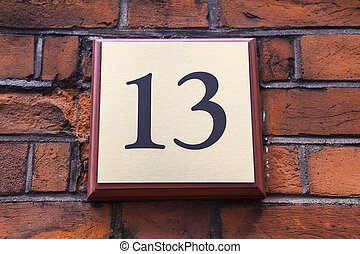 Number 13 - A plaque on a wall displaying the Number 13.