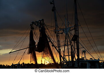 Fishing boat sunset silhouette - The silhouette of a fishing...