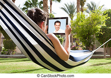 Woman In Hammock With Digital Tablet - Young Woman Lying In...