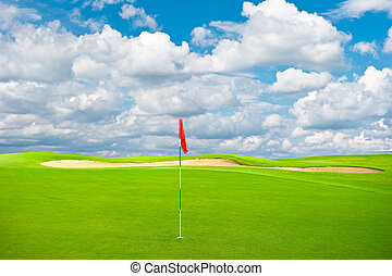 green golf field with cloudy sky background