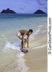 boy riding his skimboard - polynesian boy riding his skim...