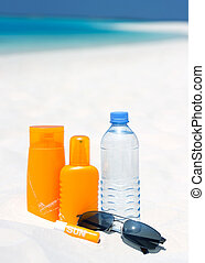 Sunglasses, water and sun protection cream on beach...