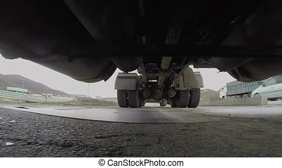 Under truck trailer ride over camera - A huge truck trailer...