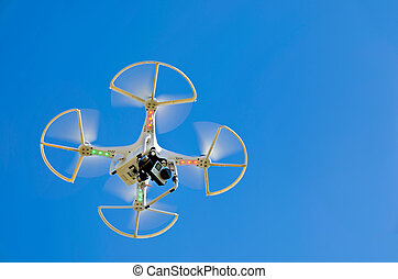 hovering white drone - Hovering white drone in a vivid blue...