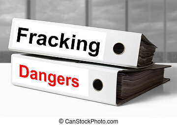 stack of office binders fracking dangers - white stack of...