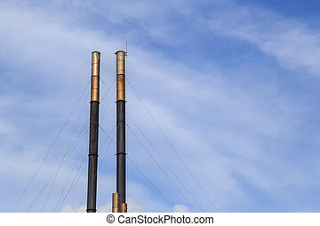 Smokestacks on blue sky background
