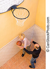 Mature couple playing basketball in patio - Cheerful active...