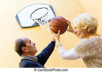 Elderly people playing with ball - Happy mature couple...