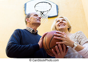 Elderly people playing with ball - Smiling adult couple...