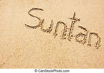 Suntan - The word suntan written in the sand on a beach