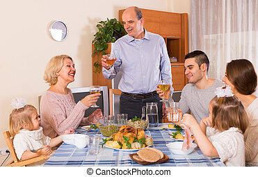 family sitting at  table for dinner