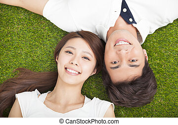 Top view of young couple in love lying together on the grass