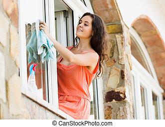 Happy woman washing windows indoor