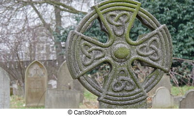 A mossy gravestones in the cemetery It has a circle with...