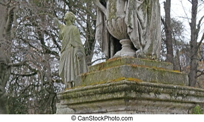 One of the old and mossy statues in the cemetery. It is a...