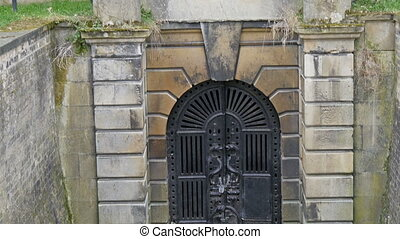 The big black gate on basement in the cemetery It is the...