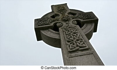 Big cross with carvings tombstones in the cemetery Lots of...