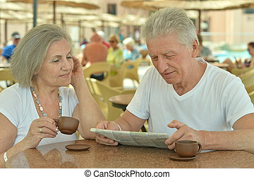 Senior couple drinking coffee outside at the resort during...