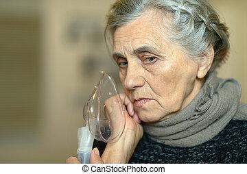 Woman making inhalation - Senior woman making inhalation on...