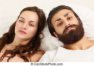 Couple strained relations, lying on bed with sad expression