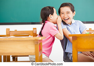 happy little girls whispering and sharing a secret  in classroom